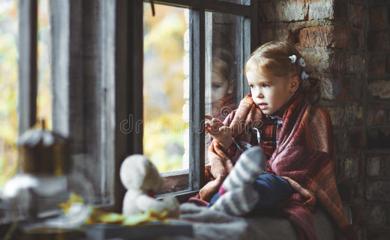 Child girl looking through window at nature autumn. Child girl looking through the window at the beautiful nature autumn gold royalty free stock photography
