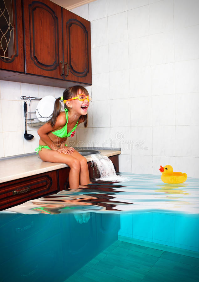 Child girl make mess, flooded kitchen imitating swimming pool, f stock images