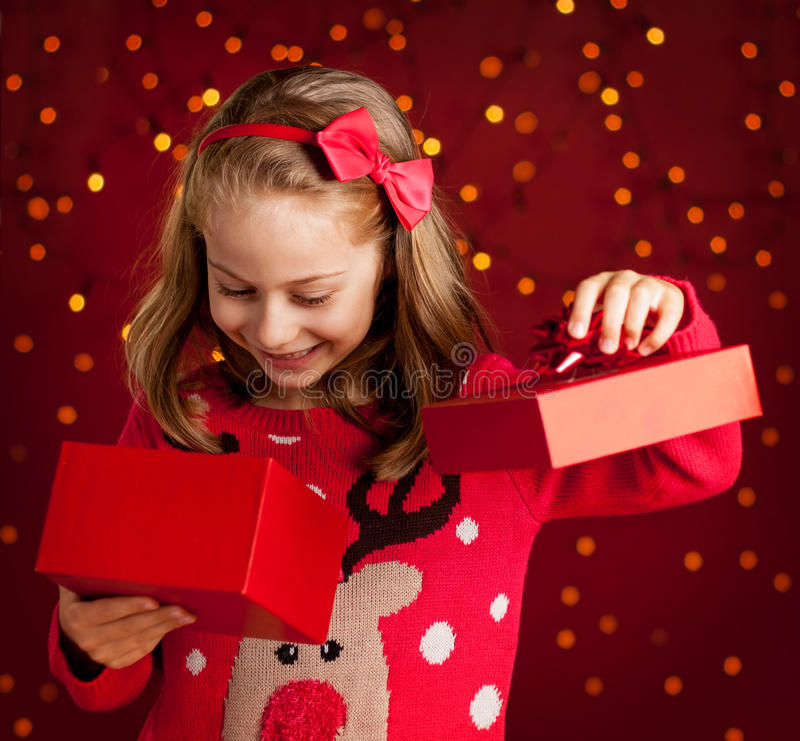 Child girl opens christmas present on dark red with lights. Christmas - happy smiling six years old blond caucasian child girl opens present on dark red royalty free stock image