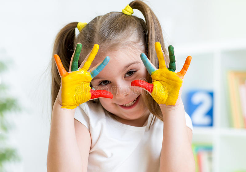 Child girl with painted fingers. At home stock images