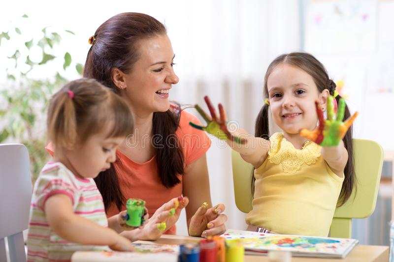 Child girl with painted hands. Kids drawing and coloring with teacher in daycare center. royalty free stock photos