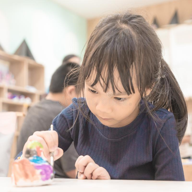 A child girl is painting doll in art class. Room royalty free stock photography