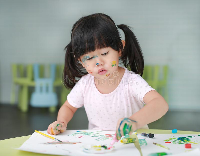 Child girl painting with paintbrush and water colors royalty free stock images