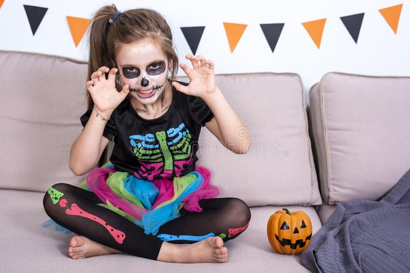 A child girl in a costume of skeleton is sitting on the sofa and frightening. Halloween party decoration. A child girl with pirate hat blowing balloon to prepare stock images