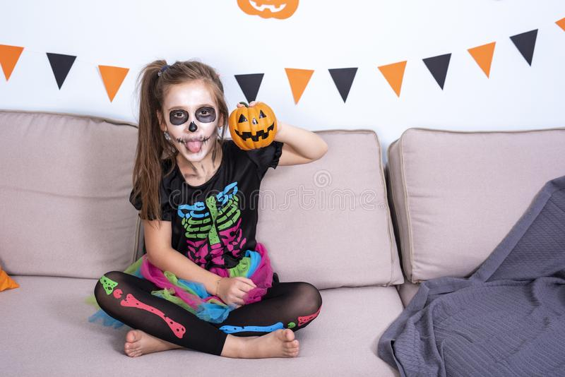A child girl in a costume of skeleton holding pumpkin Jack-o`-lantern in hand. Halloween party decoration. A child girl with pirate hat blowing balloon to royalty free stock photos