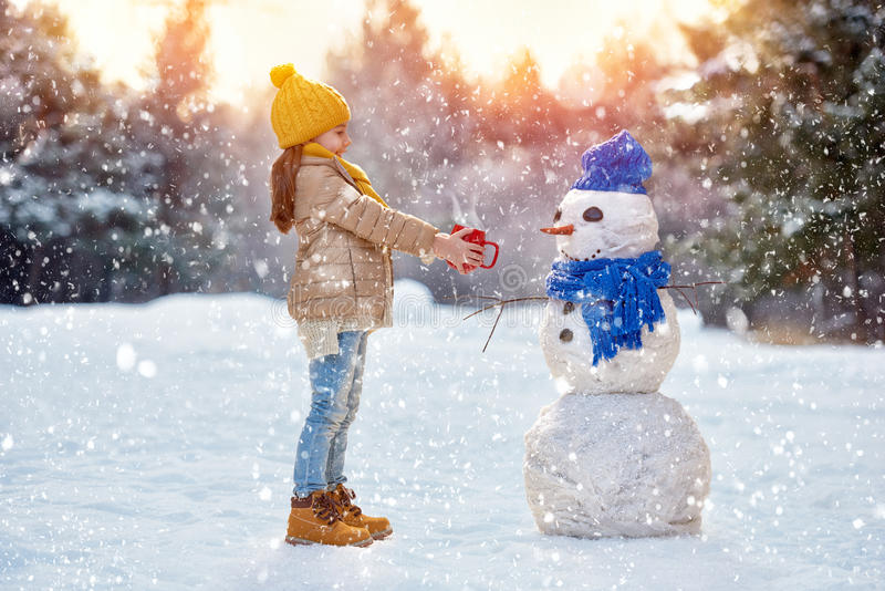 Child girl plaing with a snowman royalty free stock image