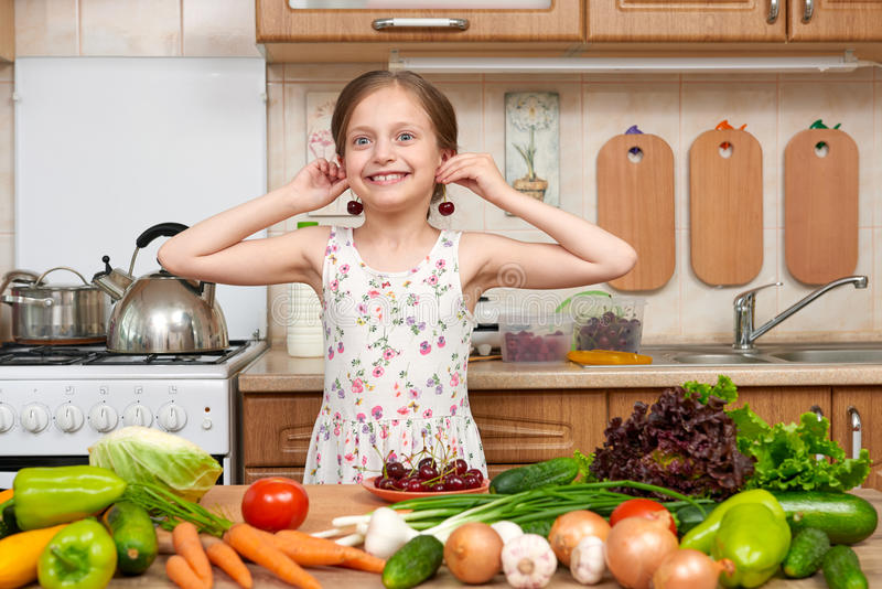Child girl play and having fun with cherries, fruits and vegetables in home kitchen interior, healthy food concept royalty free stock photo