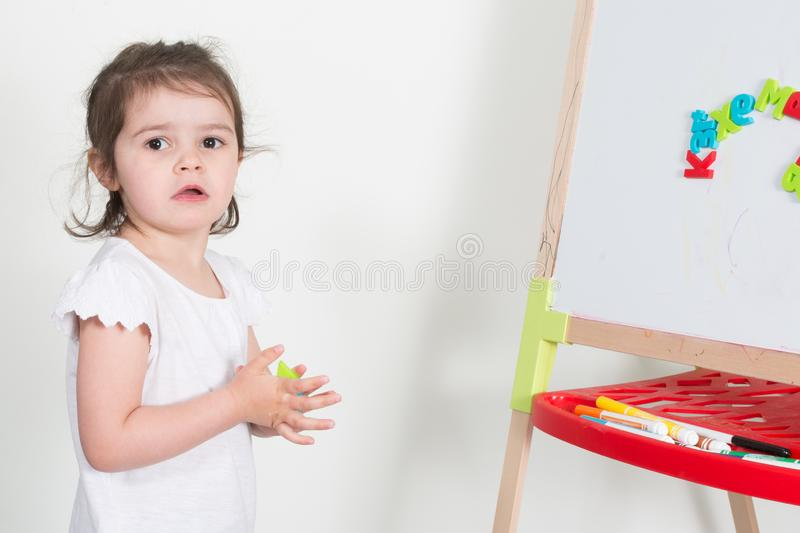 child girl play teacher with toy blackboard in school royalty free stock photos