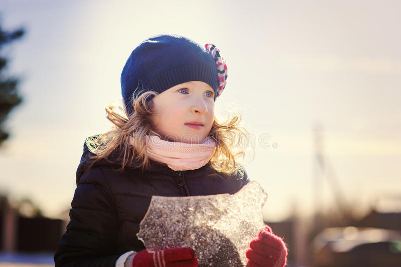 Child girl playing with block of ice on winter walk royalty free stock photos