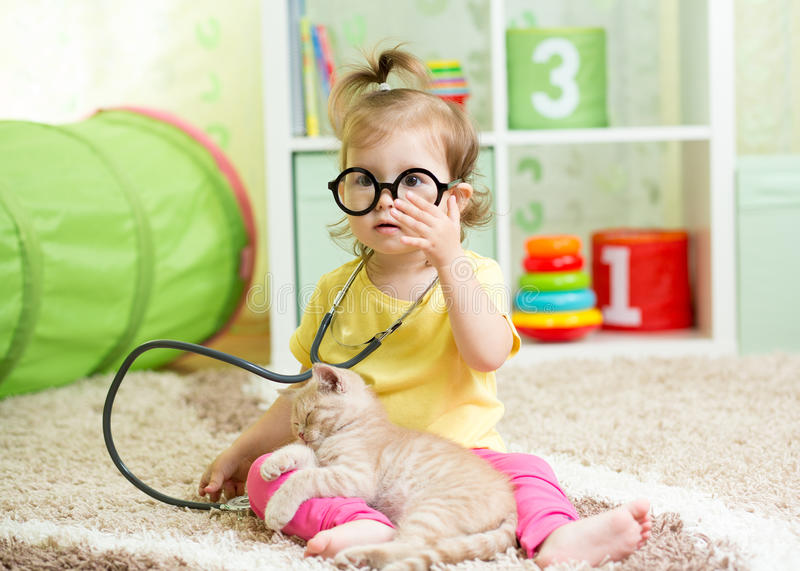 Child Girl Playing Doctor With A Cat In Nursery stock photos