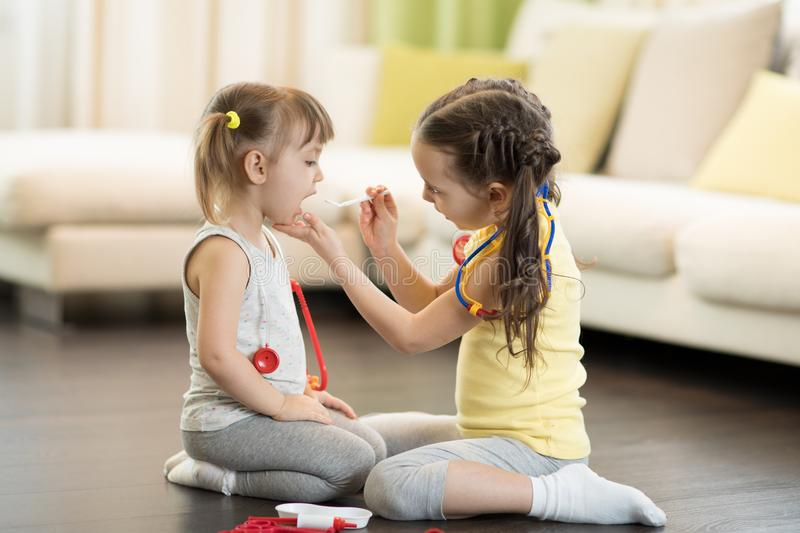 Child girl, playing doctor with her little sister at home in living room royalty free stock photo