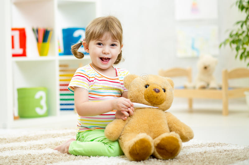 Child girl playing doctor with plush toy at home stock photography