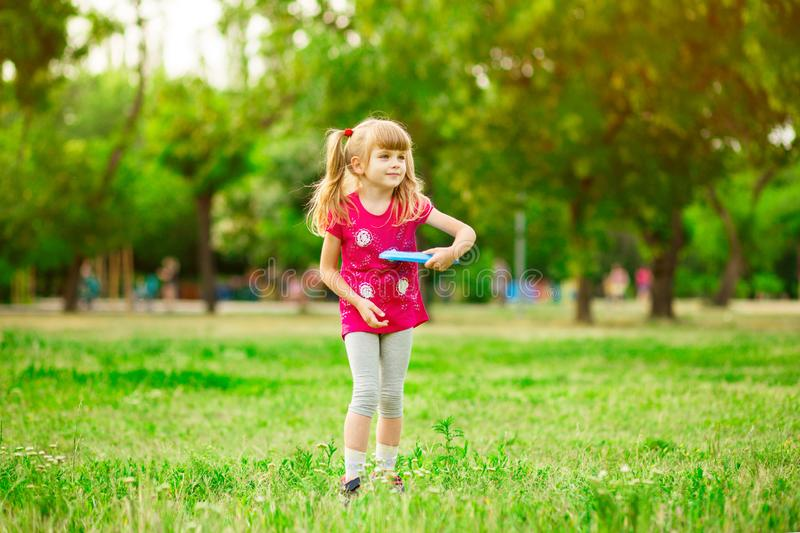 Child girl playing with a frisbee in park stock photography