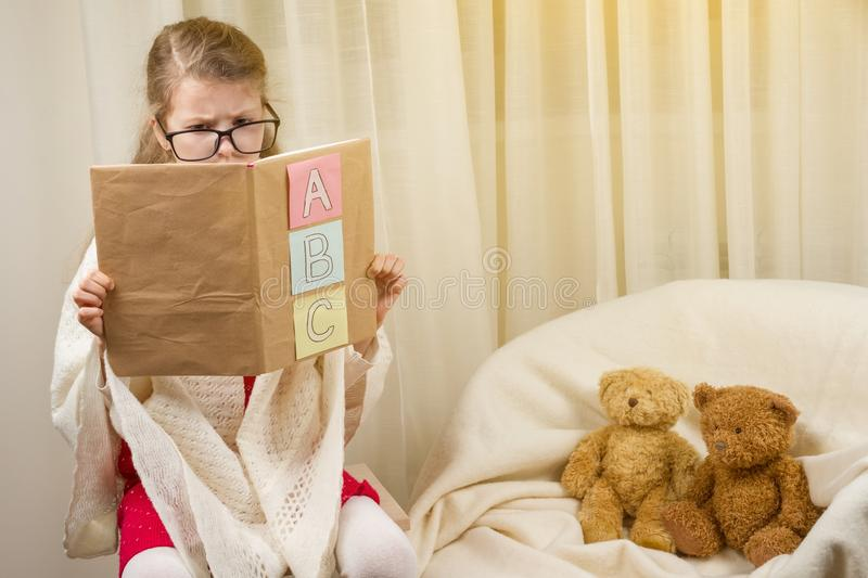 Child girl playing a school teacher with teddy bears at home. royalty free stock image