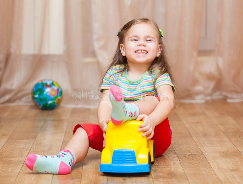 Child girl playing with a toy car on floor. At home stock image