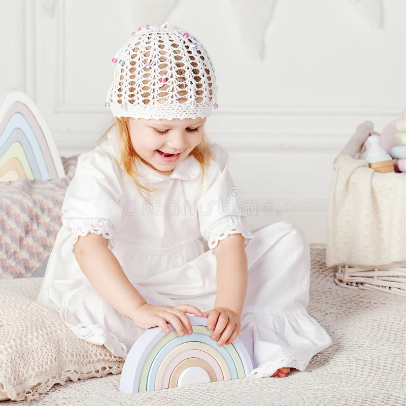 Child girl playing with a wooden toy pyramid. Little cute girl with  natural toys stock photography