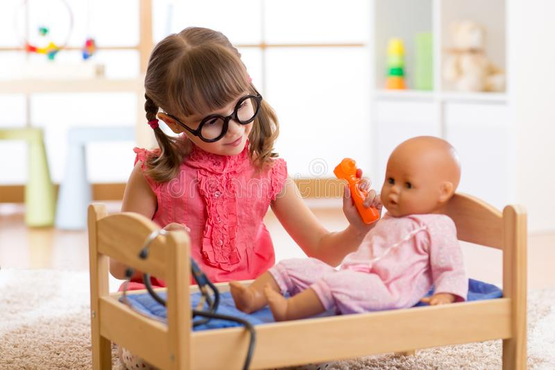 Child girl plays doctor examining baby doll patient with toy otoscope royalty free stock photo