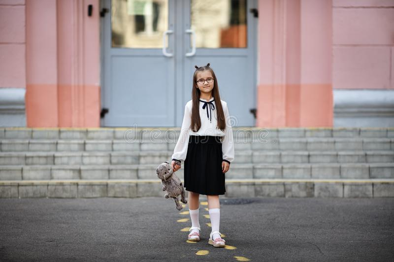 Girl with plush toy. Child girl with plush toy against school background. Back to school. Selective focus stock images