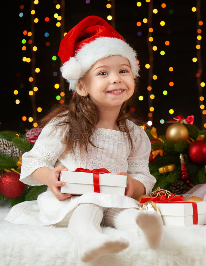 Child girl portrait in christmas decoration, happy emotions, winter holiday concept, dark background with illumination and boke li royalty free stock image