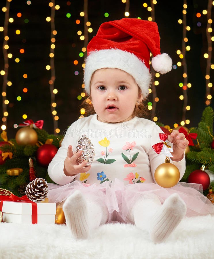 Child girl portrait in christmas decoration, happy emotions, winter holiday concept, dark background with illumination and boke li royalty free stock photos
