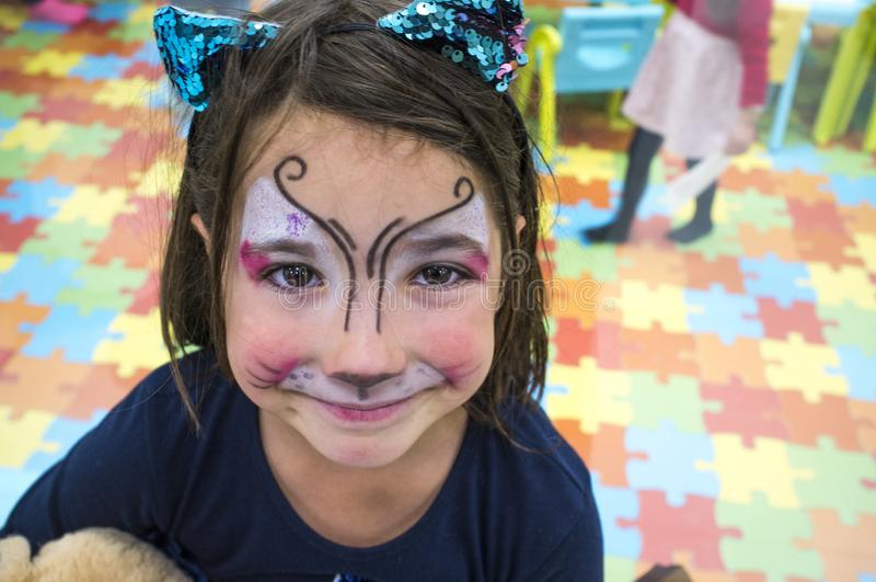 Child girl posing face painted during at Children Playroom. High angle shot stock photos
