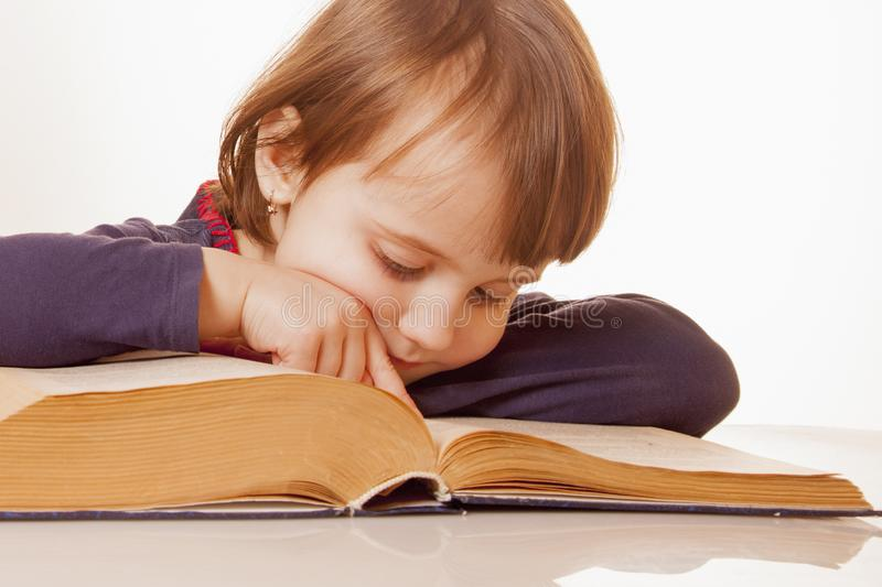 Child girl reading a book as symbol of learning, knowledge and development.  royalty free stock images