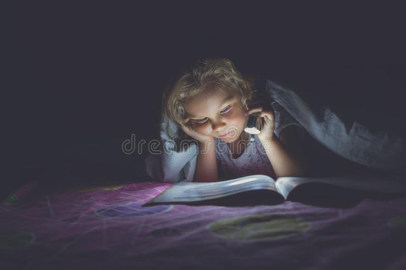 Child under a blanket with a flashlight reading royalty free stock photo