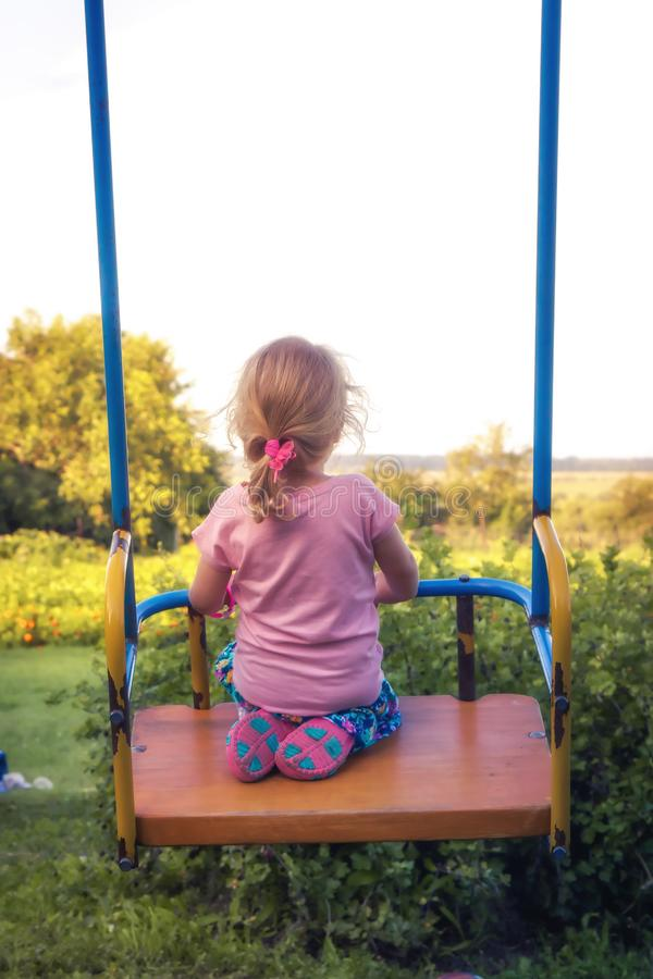Child girl rear view swinging looking in to the distance countryside happy carefree childhood lifestyle royalty free stock images