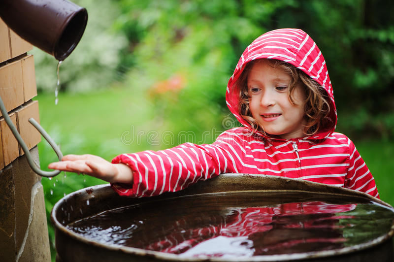 Child girl in red raincoat playing with water barrel in rainy summer garden. Water economy and nature care. Concept stock image