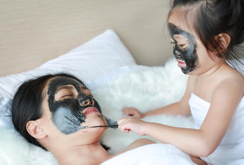 Child girl removed black mask from her mother, clean face.  stock photos