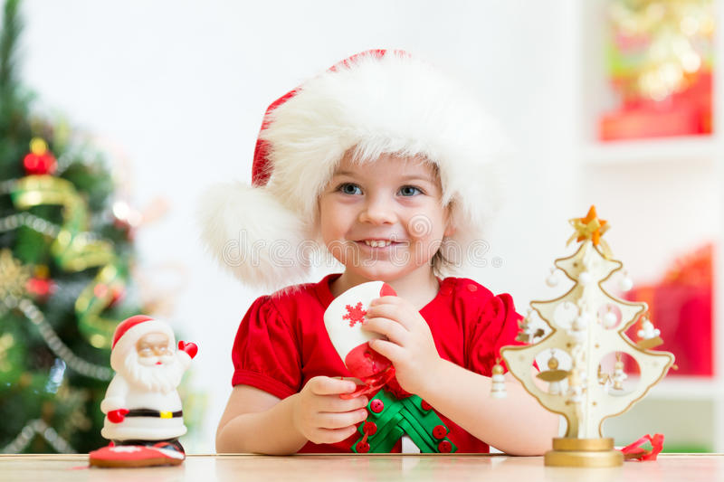 Child girl in Santa hat holding Christmas cookies. Smiling kid girl in Santa Christmas hat royalty free stock photos