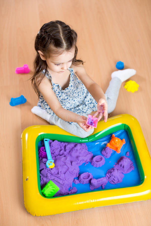 Child girl sculpts from kinetic sand in play room. Preschool. royalty free stock photos