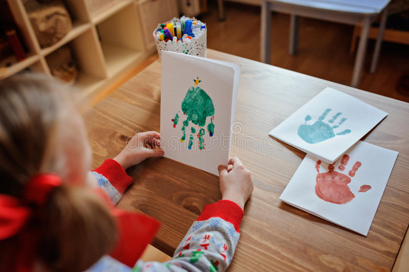 Child girl in seasonal sweater with handmade christmas handprints post cards. On the table at home royalty free stock photos
