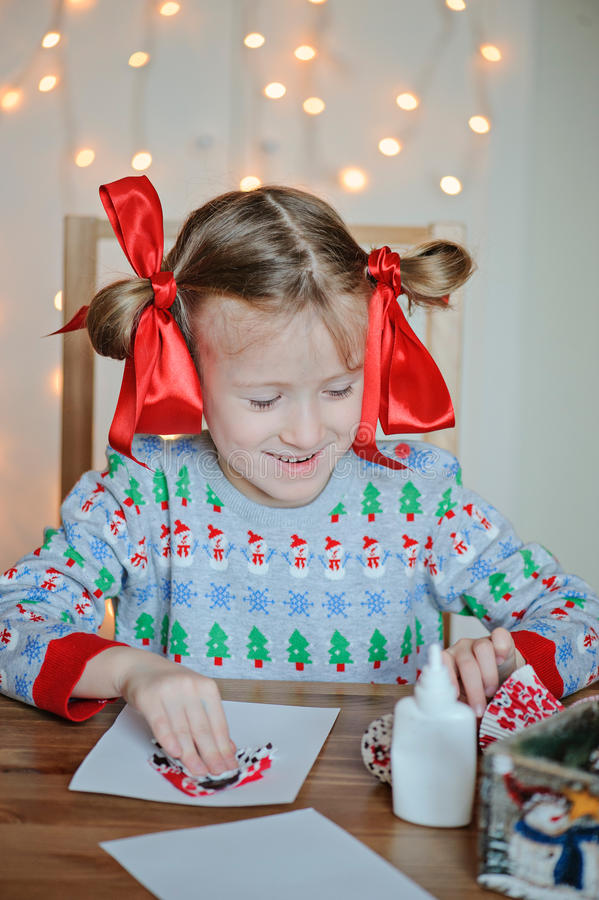 Child girl in seasonal sweater making christmas post cards. At home with light on background stock photo