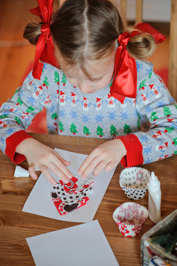 Child girl in seasonal sweater sitting and making christmas post cards at home. Child girl with red bows in seasonal sweater sitting and making christmas post royalty free stock image