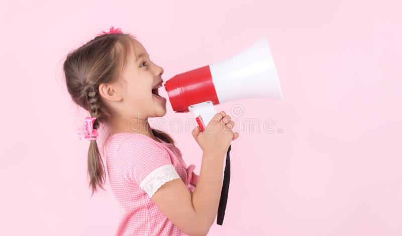 Child Girl Shouting Through Megaphone on Pink Background. Communication Concept stock photography