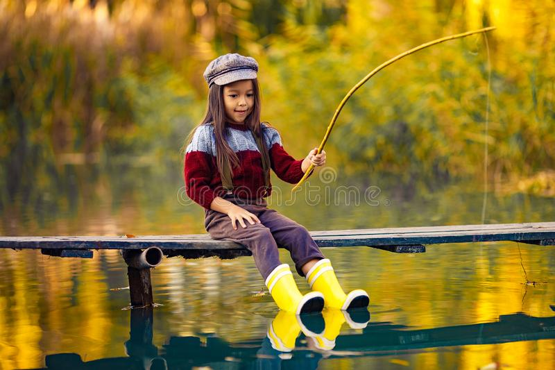 Child girl sits on wooden fishing bridge and catches fish in autumn. royalty free stock photos