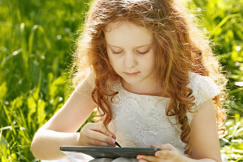 Child girl sitting on grass and playing tablet pc stock photography