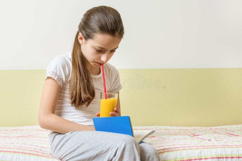 Child girl sitting at home in bed with glass of fresh orange juice and reading book stock photo