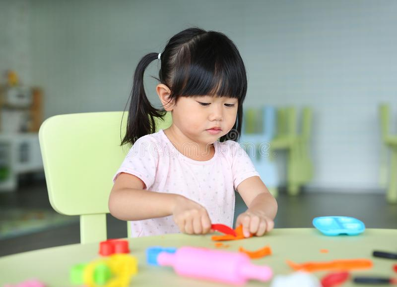 Child girl sitting at the table and plays artificial fruit royalty free stock image
