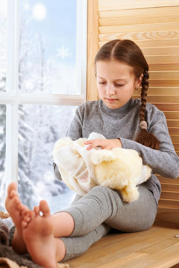 Child girl is sitting on a window sill and playing with bear toy. Beautiful view outside the window - sunny day in winter and snow stock photo