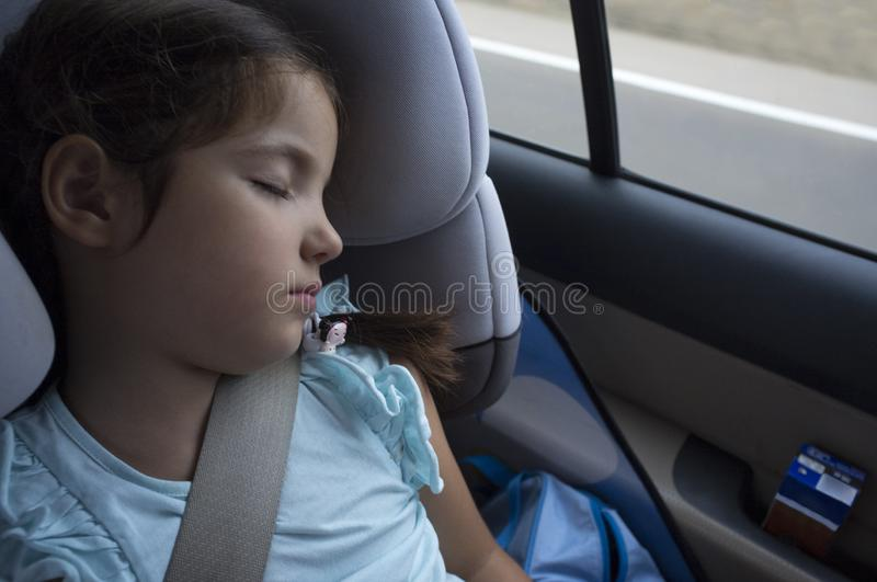 Child girl sleeping in a child safety seat during trip. She`s got a brick milkshake on car door royalty free stock image