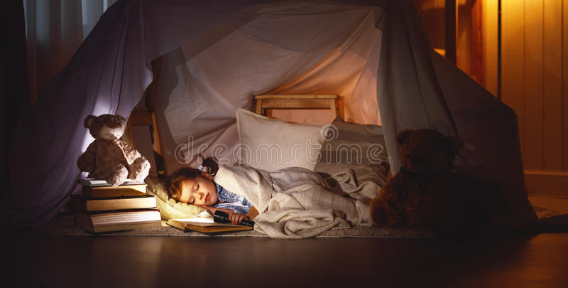 Child girl sleeping in tent with book and flashlight stock photos