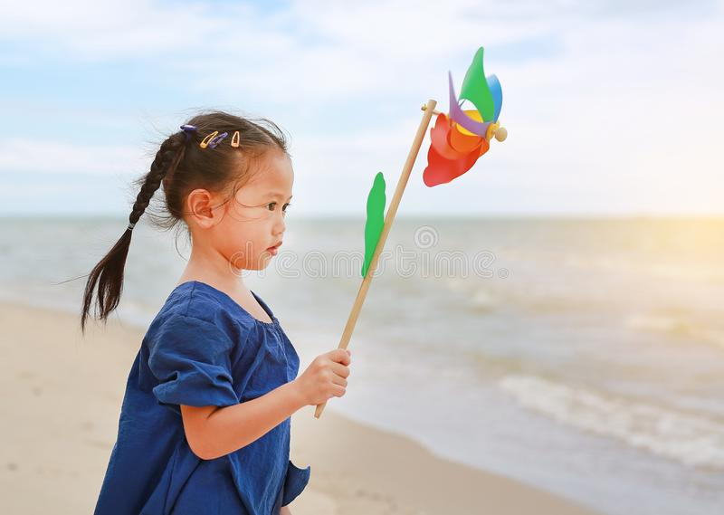 Child girl with a spinning pinwheel on the beach stock image