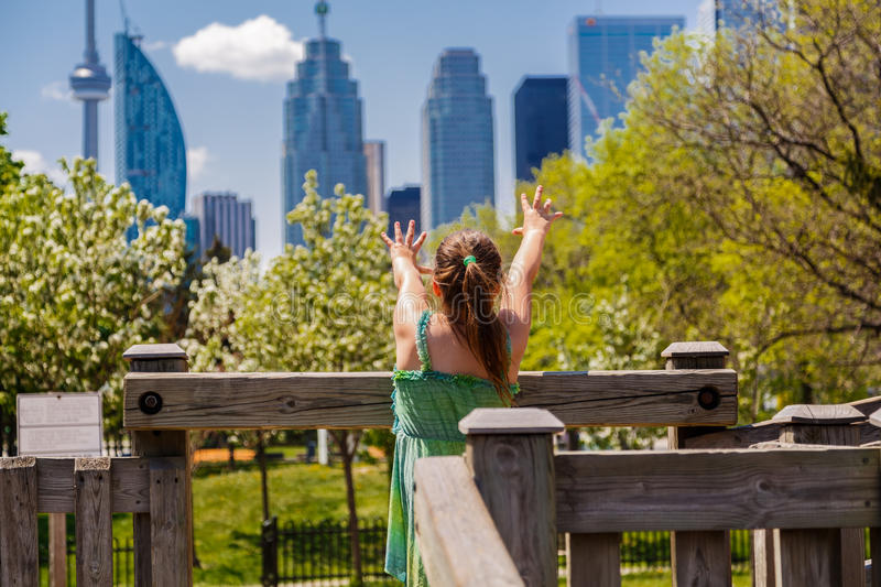 Child girl standing at kids play ground and stretched her arms toward Toronto city skyscrapers on sunny day. Little girl playing, standing at kids play ground stock images