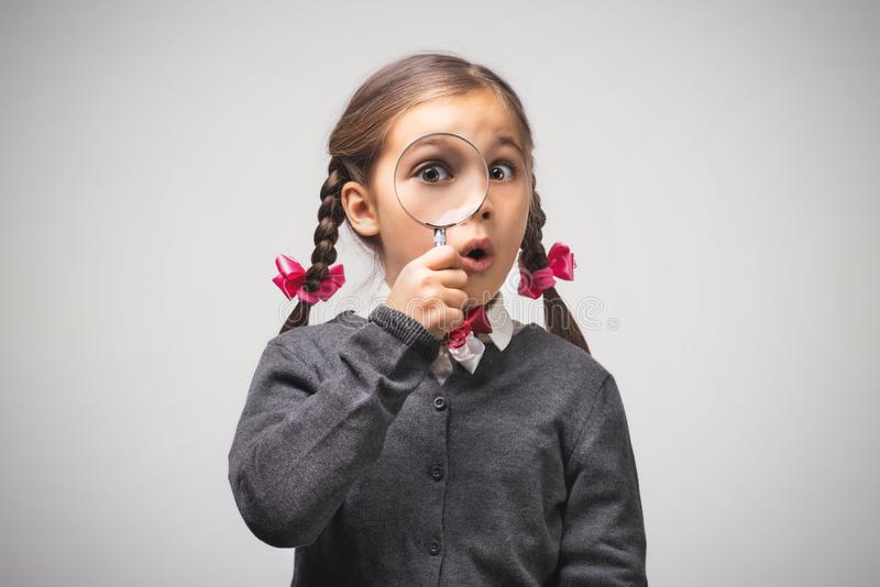 Child Girl Student Looking Through Magnifying Glass on Grey Background with Copy Space. Back to School Concept royalty free stock photos