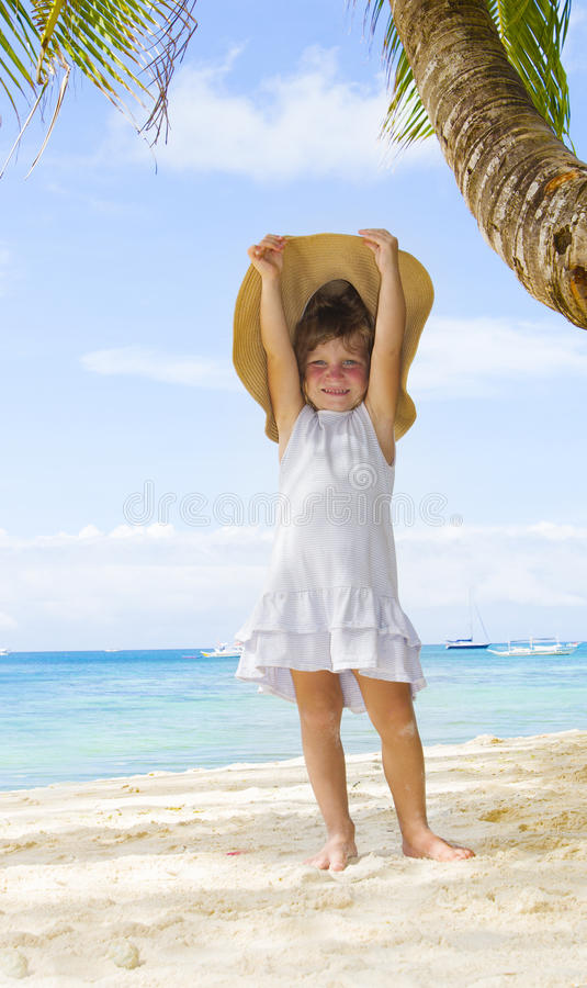Child girl in summer hat on tropical sea background stock image