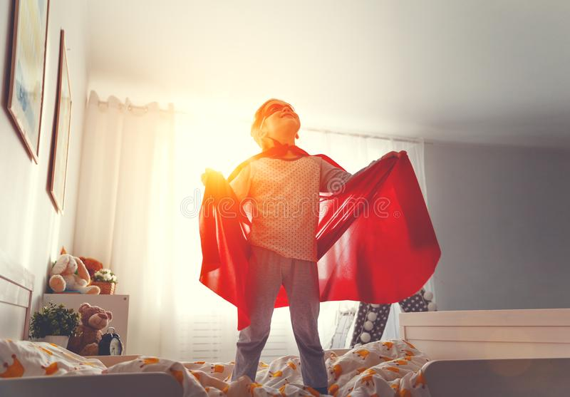 Child girl in a super hero costume with mask and red cloak stock image
