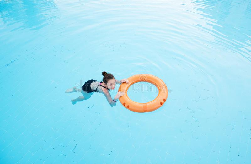 Child girl swims in the pool with lifebuoy stock photo