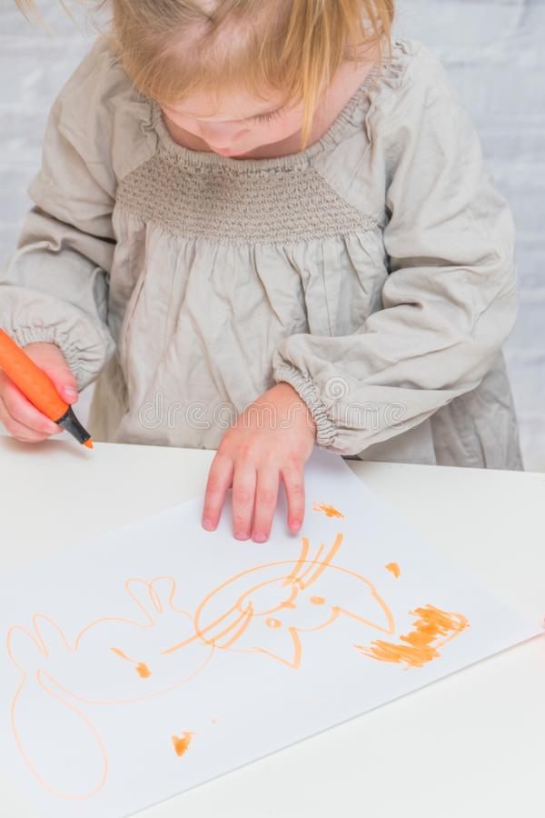Child, a girl at the table writes, draws on a piece of paper, against a white brick wall royalty free stock image